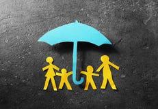 Familia de papel debajo del paraguas Foto de archivo libre de regalías