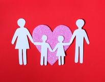 Familia de papel en corazón rosado encima en fondo rojo. Amor, niños Foto de archivo libre de regalías