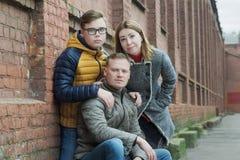 Familia de retrato de la calle del tres en el fondo de la pared del edificio de ladrillo rojo Imagenes de archivo