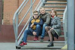 Familia de retrato urbano de la calle del tres que se sienta en las escaleras del metal en el fondo del edificio de ladrillo Imágenes de archivo libres de regalías