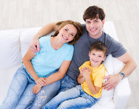 Familia de risa con el hijo en el sofá Imagenes de archivo
