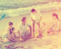 Familia de risa de seis personas que juegan junto en la playa Imagen de archivo libre de regalías