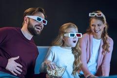 Familia de risa en los vidrios 3d que mira película y la consumición de las palomitas Imagenes de archivo