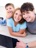 Familia de risa feliz con la computadora portátil Fotografía de archivo libre de regalías