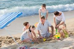 Familia de risa que juega a juegos en la playa el fin de semana Imagenes de archivo