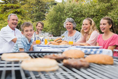 Familia de risa que tiene una barbacoa en el parque junto Fotos de archivo