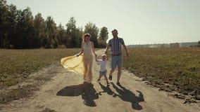 Familia de risa sonriente que corre en el campo Los padres levantan a su hijo para arriba almacen de video