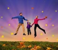 Familia de salto con el muchacho en el collage otoñal del prado Fotos de archivo