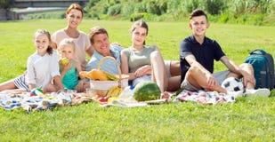 Familia de seis que tiene comida campestre al aire libre en césped verde en parque Foto de archivo
