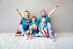 Familia de super héroes que juegan en casa foto de archivo
