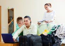 Familia de tres con el adolescente con el equipaje y el hotel f de la reserva Foto de archivo libre de regalías