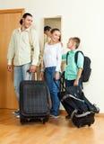 Familia de tres con el adolescente por la puerta con los bolsos Imágenes de archivo libres de regalías