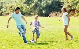 Familia de tres con la bola Foto de archivo libre de regalías