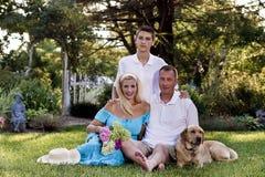 Familia de tres delante de jardín de flores Fotografía de archivo