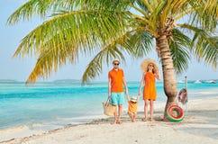 Familia de tres en la playa debajo de la palmera imagenes de archivo