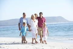 Familia de tres generaciones el día de fiesta que camina en la playa imagen de archivo libre de regalías