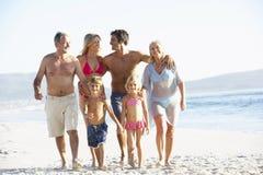 Familia de tres generaciones el día de fiesta que camina a lo largo de la playa foto de archivo