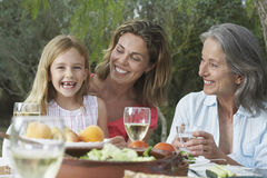Familia de tres generaciones en la tabla del jardín Fotografía de archivo
