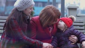 Familia de tres generaciones de mujeres sonrientes que se sientan en un banco en el parque y el abarcamiento de la ciudad Concept almacen de metraje de vídeo