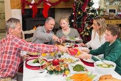 Familia de tres generaciones que cena la Navidad junto Imagenes de archivo