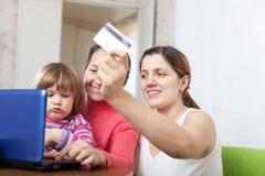 Familia de tres generaciones que compran en línea con el ordenador portátil Fotografía de archivo