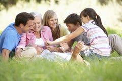 Familia de tres generaciones que se relaja en campo del verano fotografía de archivo libre de regalías