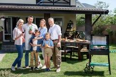 Familia de tres generaciones que se unen en césped verde y que sonríen en la cámara Imagen de archivo libre de regalías
