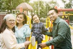 Familia de tres generaciones que sonríe en el patio imagenes de archivo