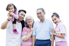 Familia de tres generaciones que sonríe en estudio imagenes de archivo