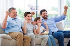 Familia de tres generaciones que ven la TV fotografía de archivo