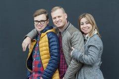 Familia de tres personas de abarcamiento que se colocan en el fondo negro de la pared Fotografía de archivo libre de regalías