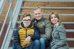 Familia de tres personas de abrazo que se sientan en las escaleras del metal en el fondo del edificio de ladrillo Foto de archivo libre de regalías