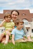 Familia de tres personas en césped delante de la casa Imagenes de archivo