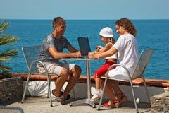 Familia de tres personas que se reclinan sobre el mar Imagen de archivo libre de regalías