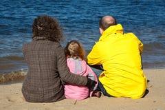 Familia de tres personas que se sientan en la arena Imágenes de archivo libres de regalías