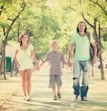 Familia de tres que camina en parque del verano Fotografía de archivo