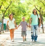 Familia de tres que camina en parque del verano Imagen de archivo