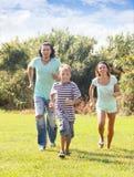 Familia de tres que corren en el parque Fotos de archivo