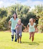 Familia de tres que corren en hierba Imagen de archivo libre de regalías