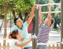 Familia de tres que entrena en barra de la barra de la barbilla-para arriba Imagen de archivo libre de regalías