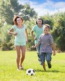 Familia de tres que juegan en fútbol Fotos de archivo libres de regalías