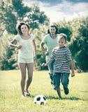 Familia de tres que juegan en fútbol Foto de archivo libre de regalías