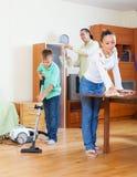 Familia de tres que limpian en hogar Imagen de archivo libre de regalías