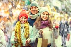 Familia de tres que presentan en el mercado de la Navidad Imágenes de archivo libres de regalías