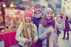 Familia de tres que presentan en el mercado de la Navidad Foto de archivo libre de regalías