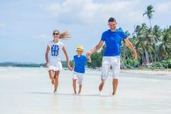Familia de tres que se divierten en la playa Imágenes de archivo libres de regalías