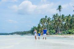 Familia de tres que se divierten en la playa Imagen de archivo libre de regalías