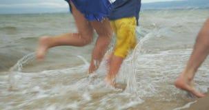 Familia de tres que se divierten que corre en la playa almacen de video