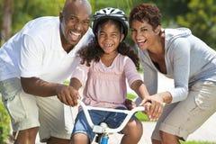 Familia del afroamericano y bici felices del montar a caballo de la muchacha Fotos de archivo