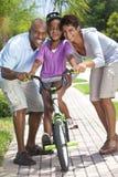 Familia del afroamericano y bici felices del montar a caballo de la muchacha Fotos de archivo libres de regalías